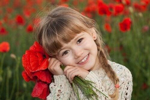 Niña-feliz-con-ramo-de-flores-rojas