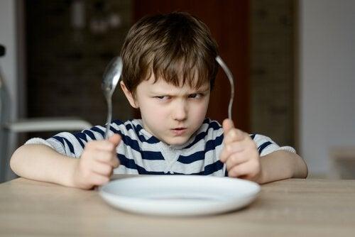 niño-con-cuchara-y-tenedor-enfadado