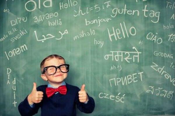 niño-feliz-con-pizarra-con-letras-muchos-idiomas
