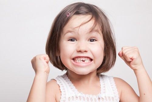 Nina feliz sonriendo y enseñando los dientes