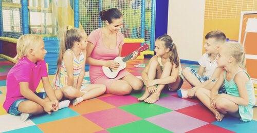 Niños alrededor de la profesora tocando la guitarra en clase de expresión musical.