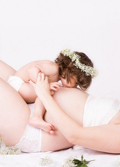 embarazada-tumbada-con-hija-besando-la-barriga