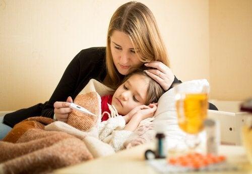 Niña con fiebre y madre preguntándose si es verdad que los niños crecen cuando tienen fiebre.