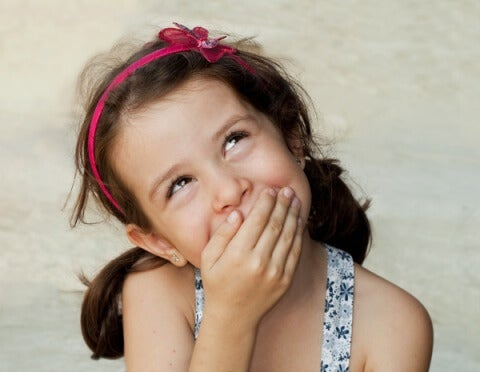 niña-riéndose-tampando-su-boca
