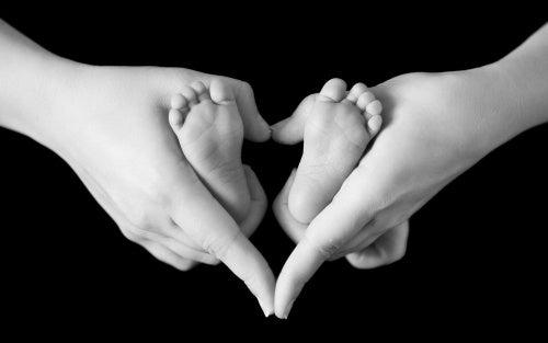 Madre cogiendo los pies de su bebé