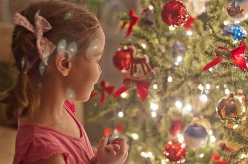 Niña mirando un árbol de navidad iluminado