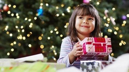Niña con un regalo bajo el árbol de navidad
