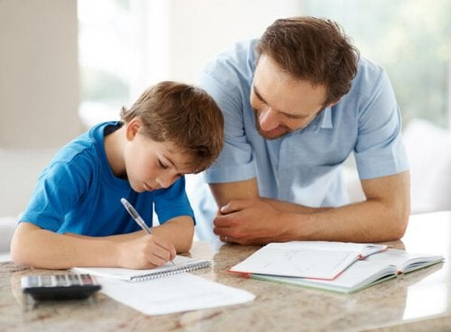 Portrait of a happy man helping his son to do homework - Indoor