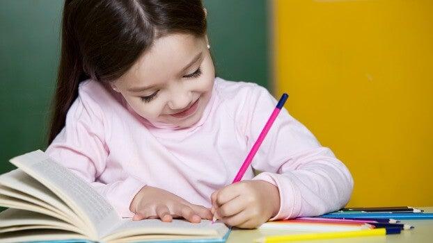 Petite fille heureuse de travailler, avec un crayon et un livre
