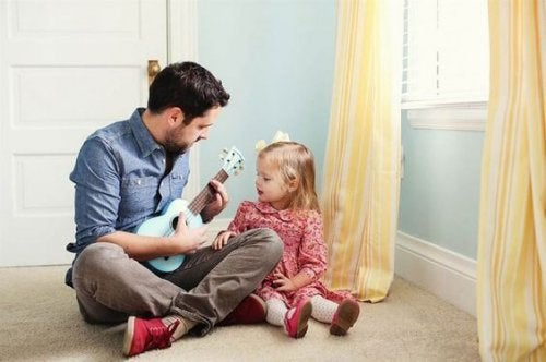 Father playing guitar to daughter