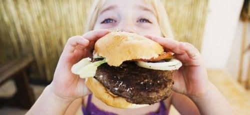 Niña comiéndose una de las hamburguesas saludables para toda la familia.