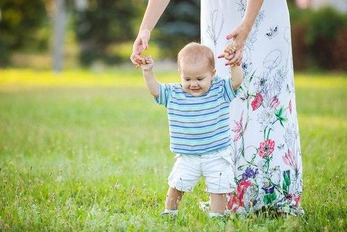 Bebé dando sus primeros pasos cogido de las manos de su madre.