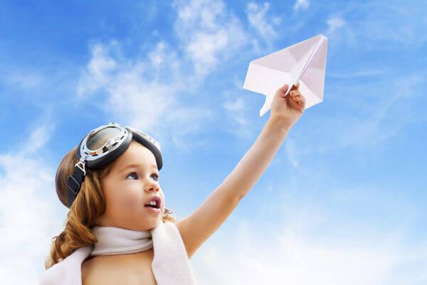 niña jugando con avión de papel