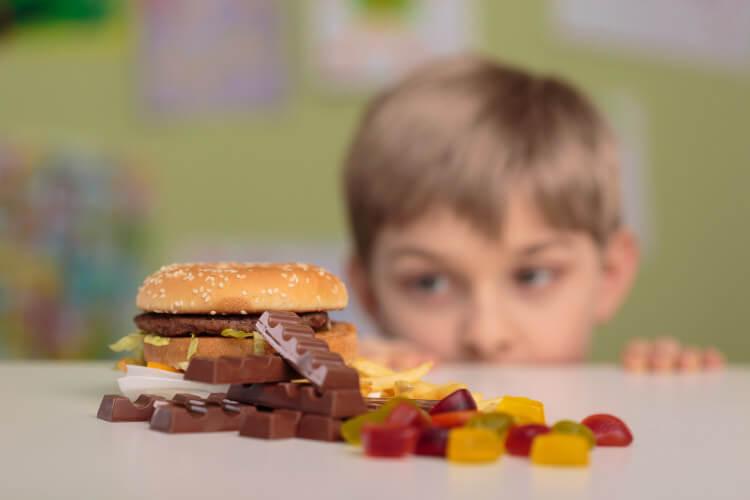 niño mirando chocolate y golosinas