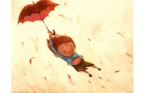 niño volando en un paraguas
