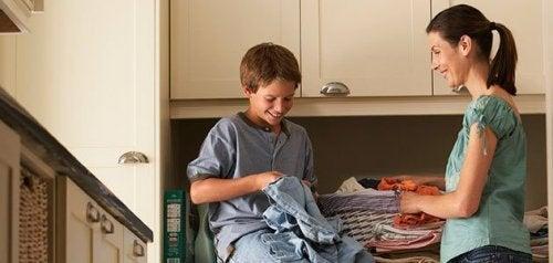 Niño doblando la ropa de la lavadora como método de sobrecorrección para modificar conductas.