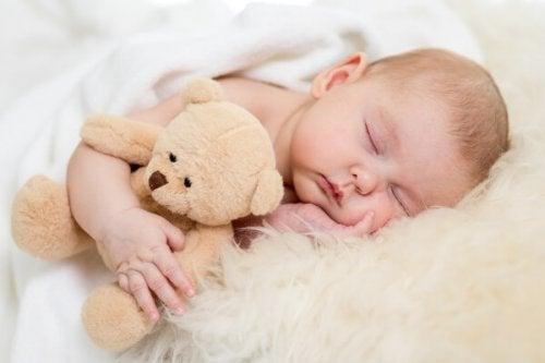 Bebé dormido en su cuna abrazando un peluche