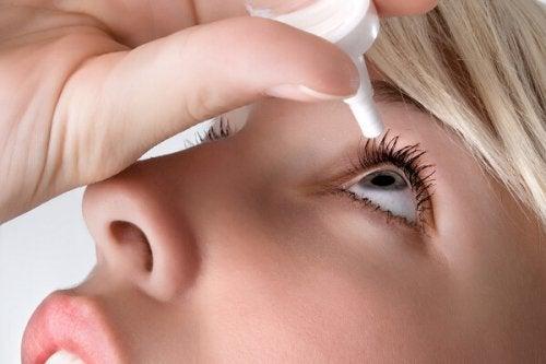 embarazada con ojos secos aplicándose lágrimas artificiales