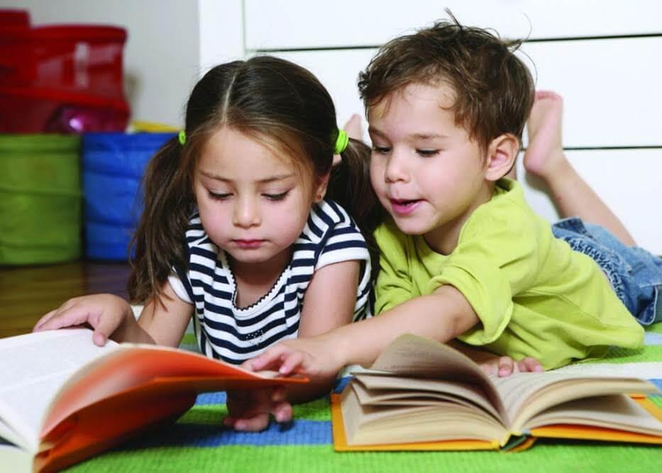 Livres et contes pour enseigner des concepts actuels, devant deux enfants couchés