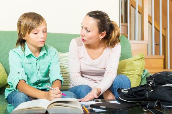 Mamá ayudando a su hijo a hacer los deberes