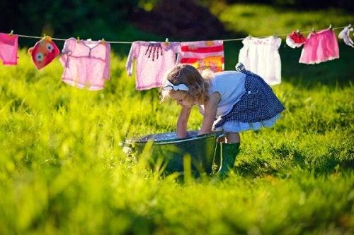 niña tendiendo la ropa