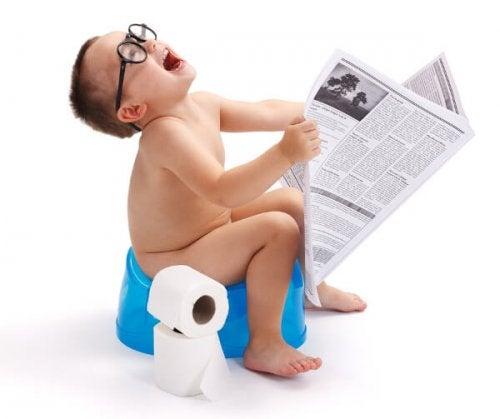 Un petit garçon sur le pot avec un journal