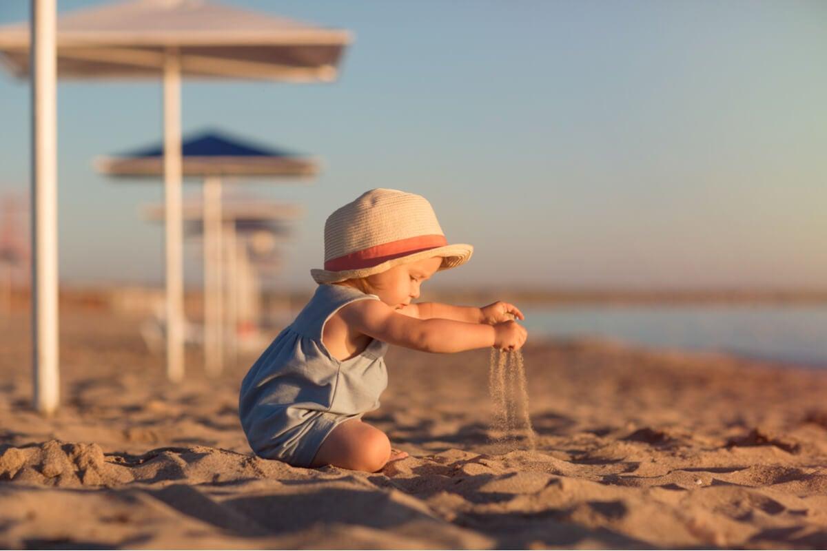 Niño con gorro jugando con la arena de la playa
