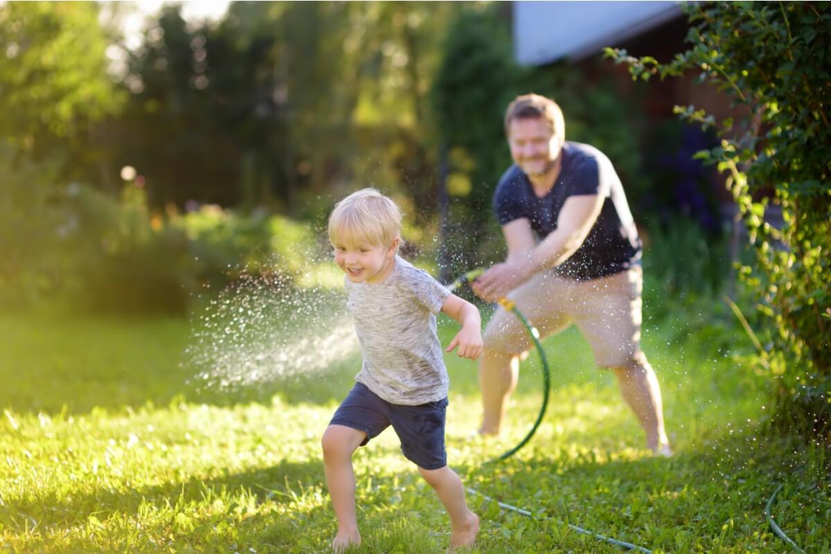 Padre mojando a su hijo con la manguera