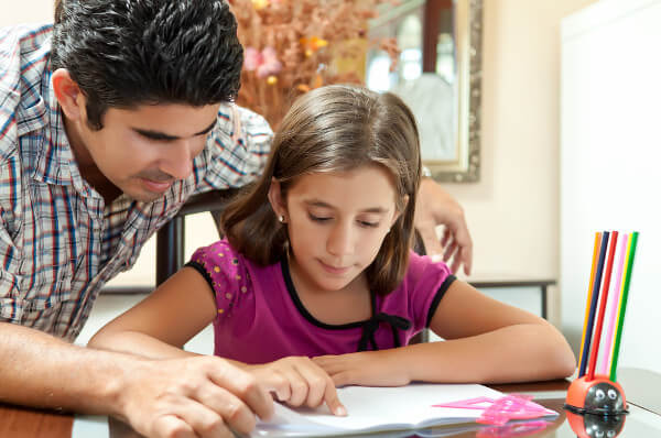 Papá ayudando a su hija a hacer los deberes