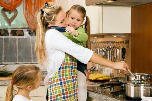 Une maman au téléphone pendant qu'elle fait la cuisine et s'occupe de petites filles