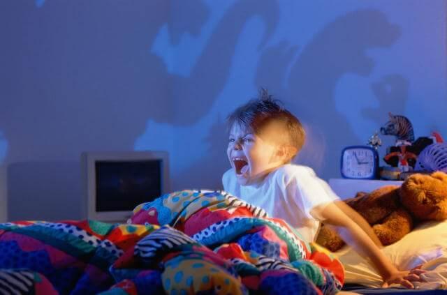 Niño en su cama gritando en medio de la noche porque tiene pesadillas.