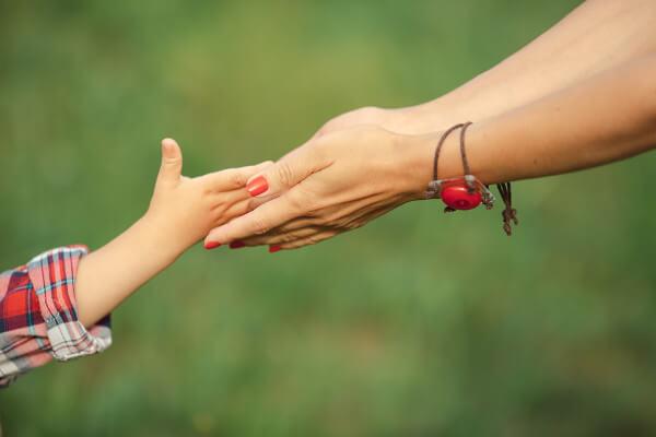 Madre e hija dándose la mano