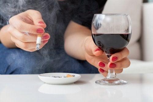 Mujer fumando y bebiendo alcohol