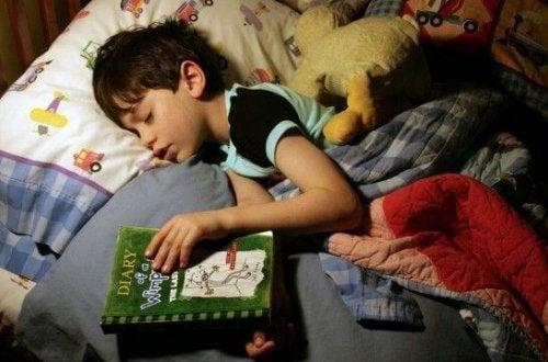 niño con un libro en la cama