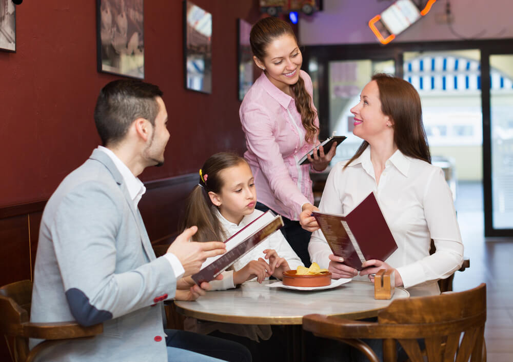 padres con su hija en un restaurante