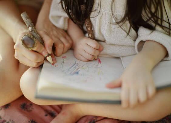 Une petite fille dessine dans un carnet, une des techniques d'apprentissage favorisant la mémorisation