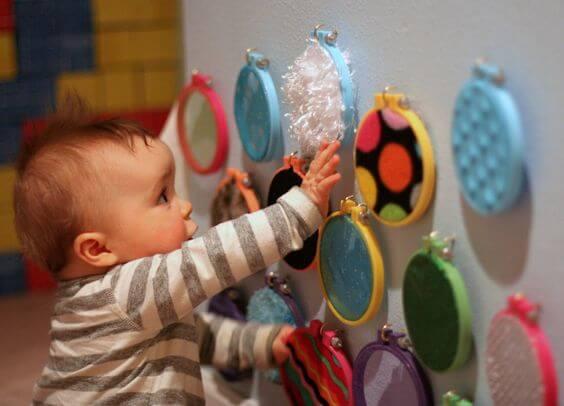 Un bébé qui touche des matières différentes sur un mur d'éveil.