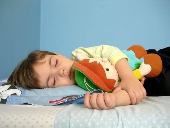 Petit garçon ensommeillé avec une peluche