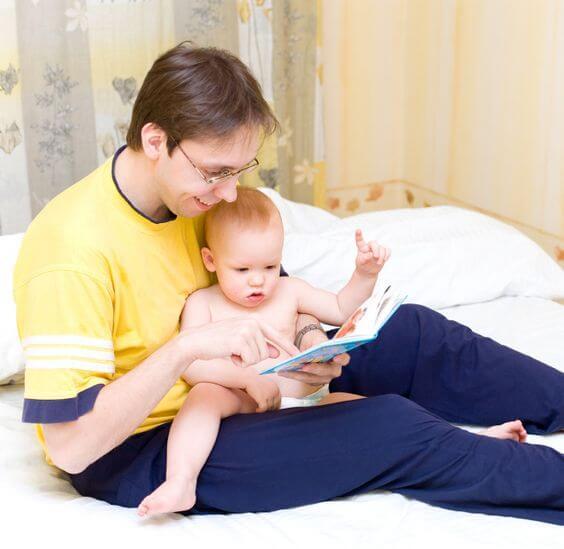 Un père avec son bébé dans les bras qui regardent un livre.