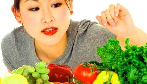 Une femme mange des fruits et légumes.