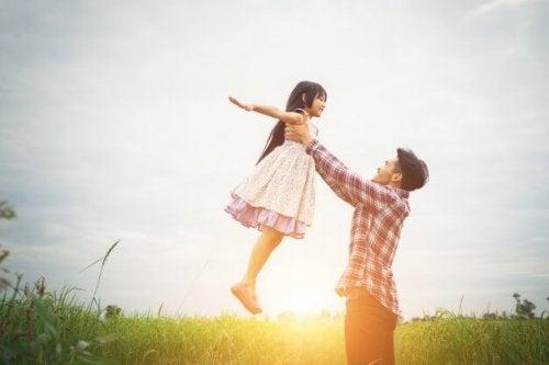 Padre elevando a su hija en el aire en el campo y poniendo en práctica la disciplina positiva.