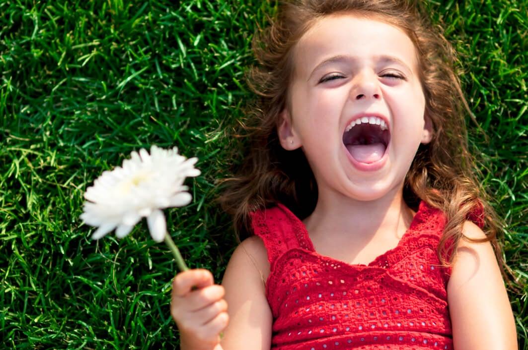 Une jeune fille allongée dans l'herbe avec une fleur dans la main.