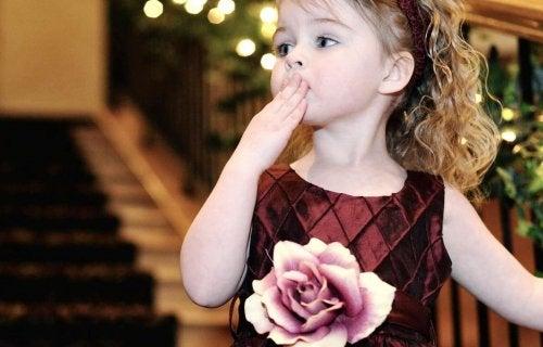 niña lanzando beso
