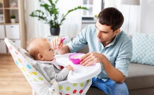 Padre dando de comer a su bebé para que tenga una excelente nutrición infantil.