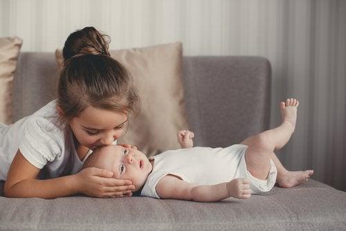 Hermana mayor dándole muchos besos a su hermano bebé.