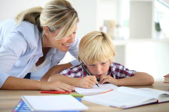 Une mère encourageant son enfant devant ses cahiers de classe