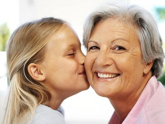 Une petite fille embrasse sa grand-mère maternelle