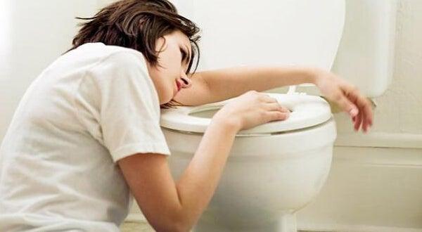 Femme prise de nausées au-dessus des toilettes