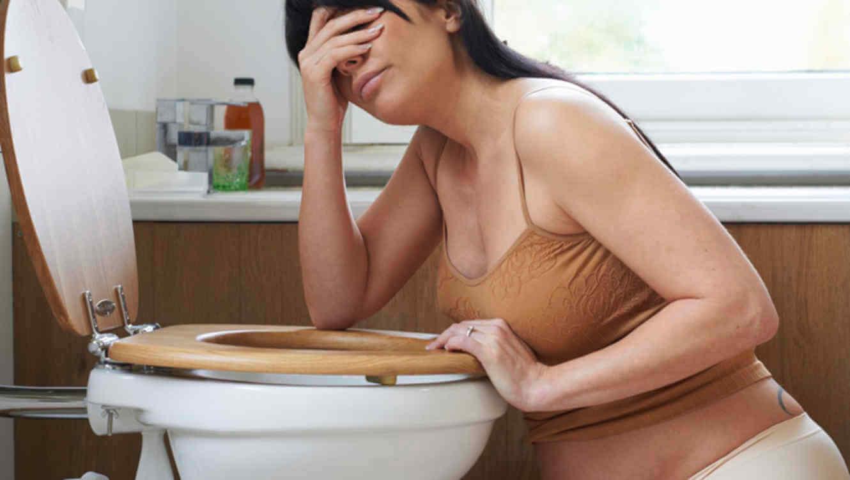 Femme enceinte dans sa salle de bain, prise de nausées au-dessus des toilettes