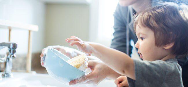 Enfant qui fait la vaisselle avec sa maman
